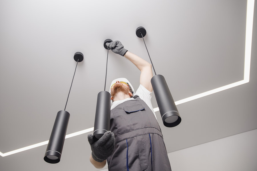 man installing ceiling lights
